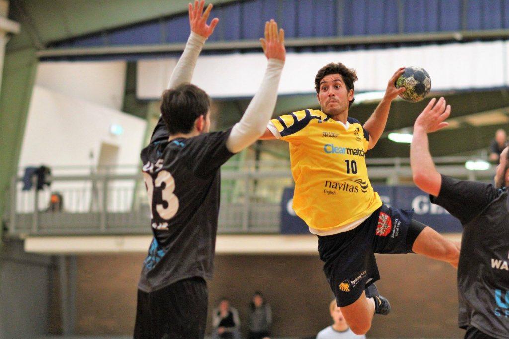 Handball player mid-air shooting at goal