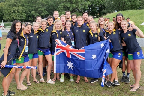 Australian beach handball teams pose with Australian flag for a team photo