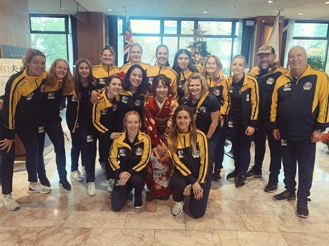 Team photo of Australian women's team at the airport dressed in national team uniforms