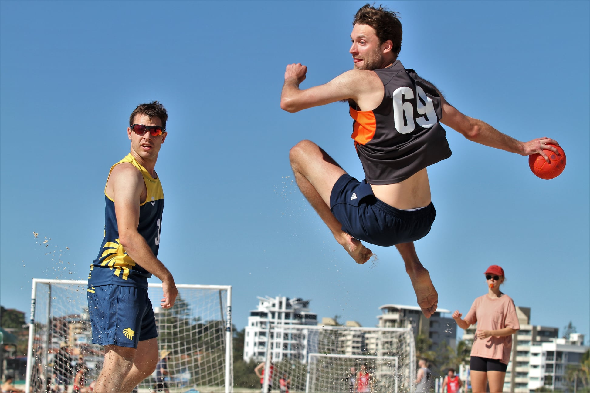 A player wearing a black singlet in mid-air about to throw a red ball in hand while another player wearing a blue singlet and sunglasses watches on. In the bacground, referee is seen with whistle in mouth