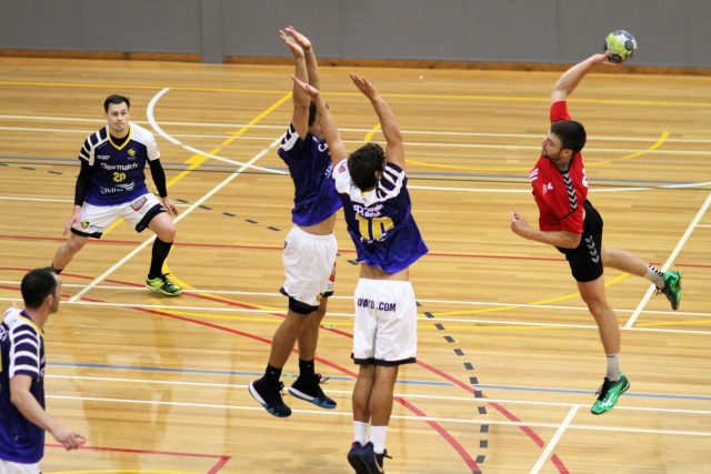 St Kilda player jump shooting towards goal and being blcoed by two sydney uni players
