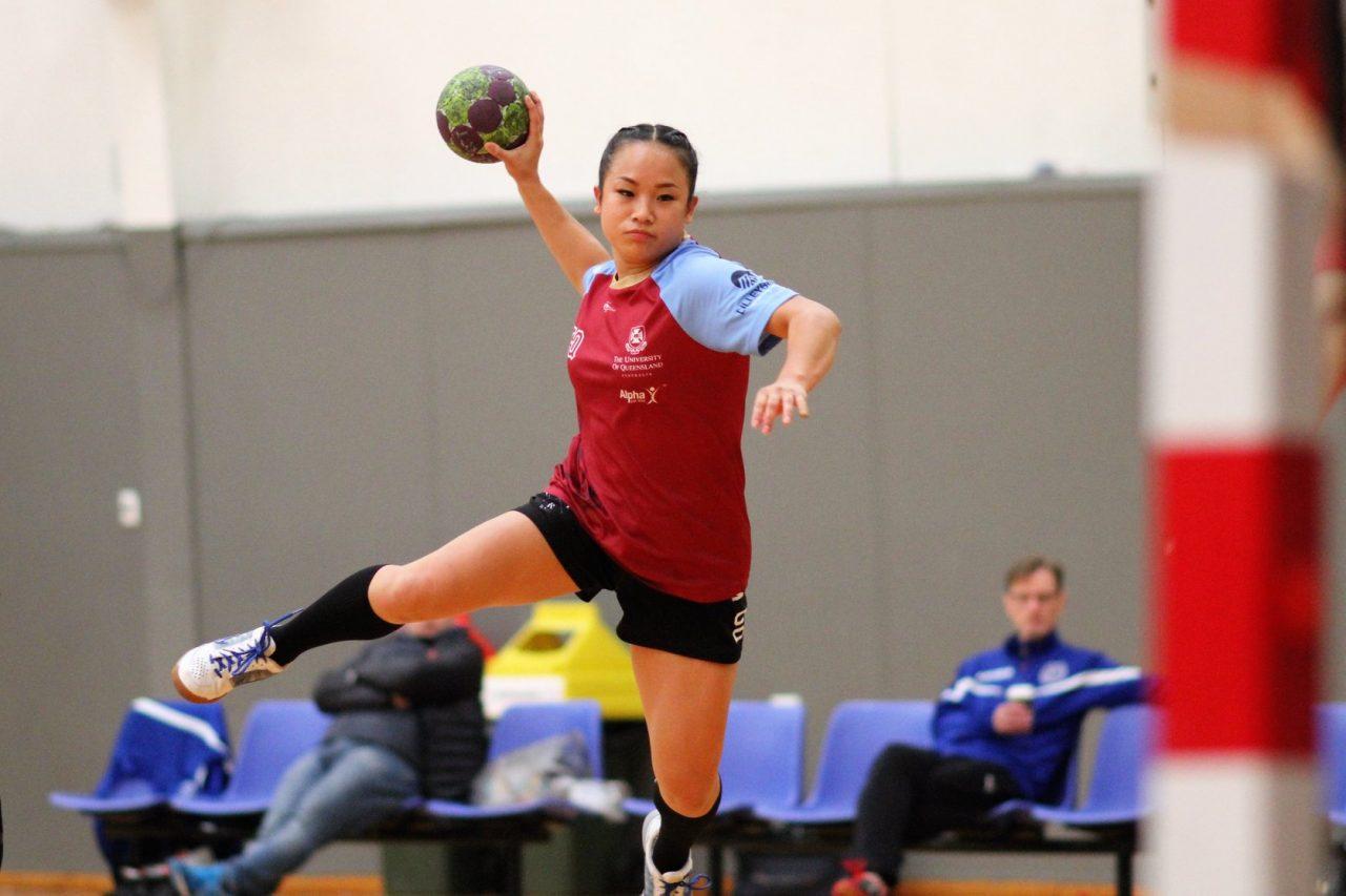 A handball player, mid-air, shooting at goal