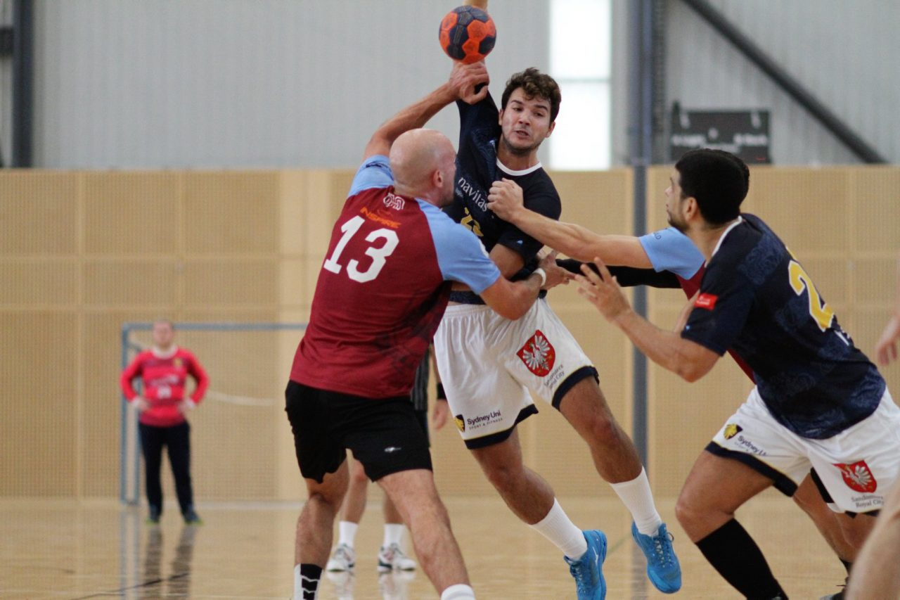 A Sydney University player, with blue shirt and white shorts attempts to throw at goal but is being held by a defender wearing a red shirt and black shorts