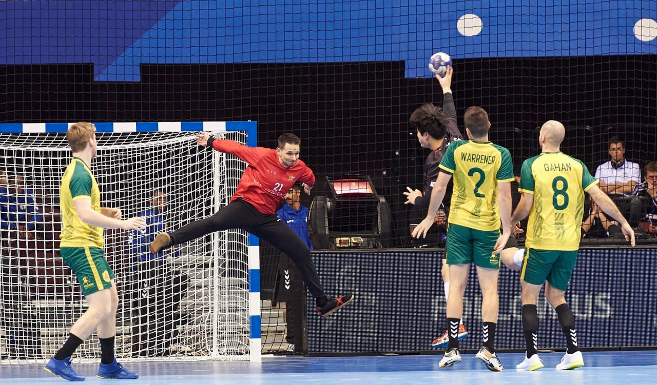 A goalkeeper wearing red is in mid-air with hands and legs spread out as a player with ball in hand throws towards the goal