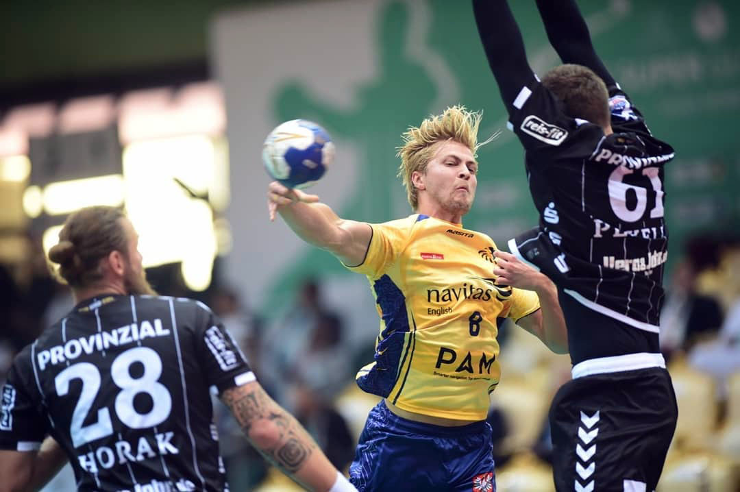 Sydney University player wearing yellow shootr around a defender, attempting to block, wearing black